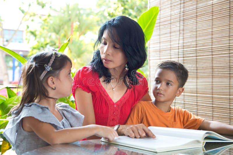 Asiatische Mutter mit junger Tochter- und Sohnlesung lizenzfreie stockfotografie