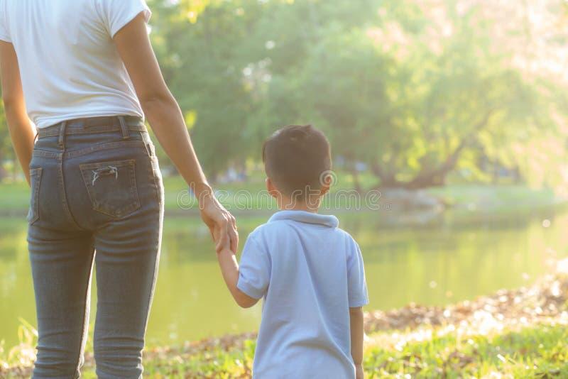 Asiatische Mutter- oder Elternteil- und Sohnholdinghand mit Liebe zusammen in der Sommerau?enseite im Park lizenzfreie stockfotos