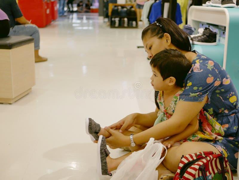 Asiatische Mutter und ihre kleine Tochter, die auf Schuhe sich setzt und sie auf eine Entscheidung vorher treffen versucht, ob ma lizenzfreie stockfotografie