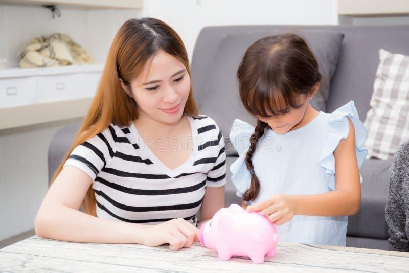 Asiatische Mutter und Tochter, die Münze in Sparschwein, in Mutter und in ki einsetzt stockfotos