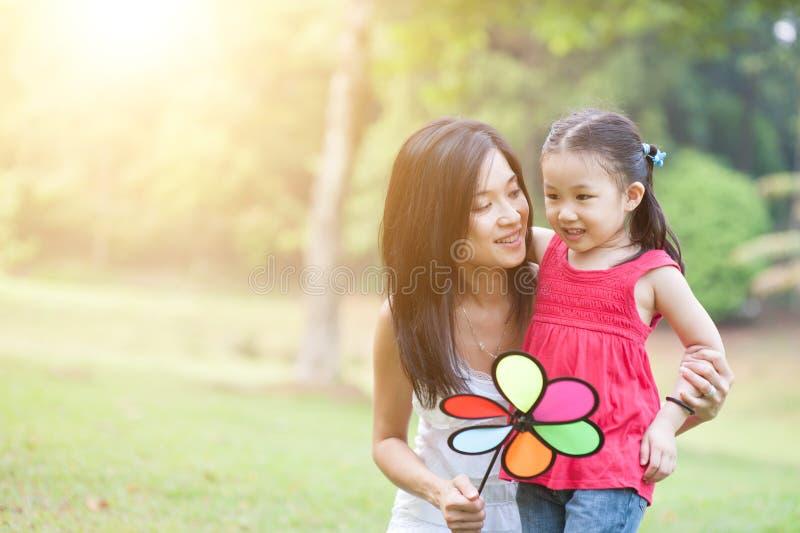 Asiatische Mutter und Tochter, die Windmühle im grünen Park spielt lizenzfreies stockbild