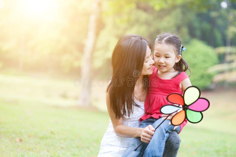 Asiatische Mutter und Tochter, die Windmühle im Park spielt lizenzfreie stockfotos