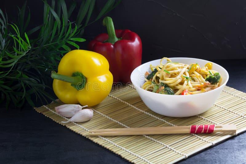 Asiatische Nahrung, eine Schüssel Aufruhrfischrogen Udonnudeln mit Gemüse und Sojasoße auf einer Bambusmatte, schwarzer Hintergru lizenzfreie stockbilder