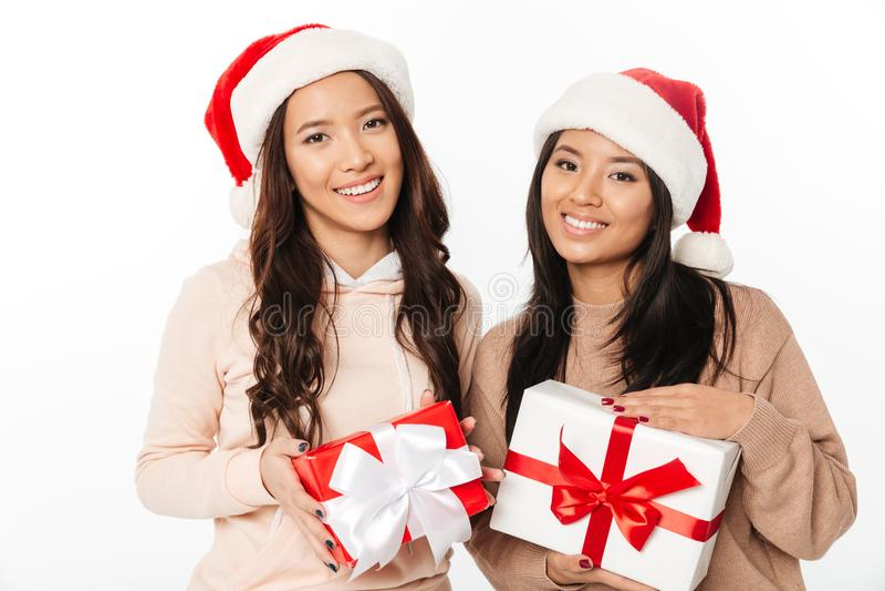 Asiatische nette Damenschwestern, die Weihnachts-Sankt-Hüte tragen lizenzfreie stockfotos