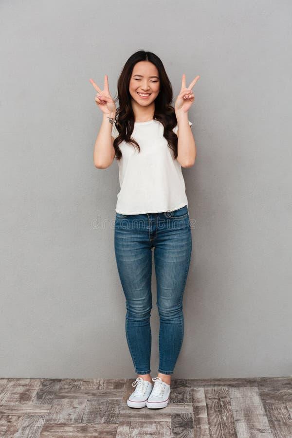 Asiatische nette Frau im zufälligen T-Shirt und Jeans Lächeln und gesturi stockfoto
