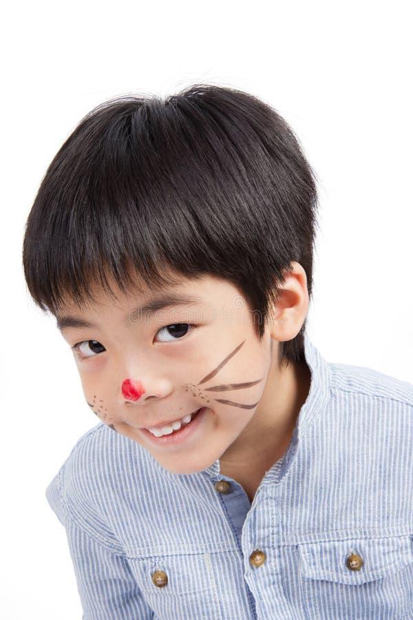 Asiatische nette Jungenfarbe sein Gesicht und Lächeln stockfoto