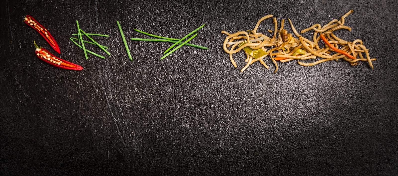Asiatische Nudeln mit grünen Schnittlauchen und rotem Paprika auf dunklem Schieferhintergrund, Draufsicht, Fahne lizenzfreie stockbilder