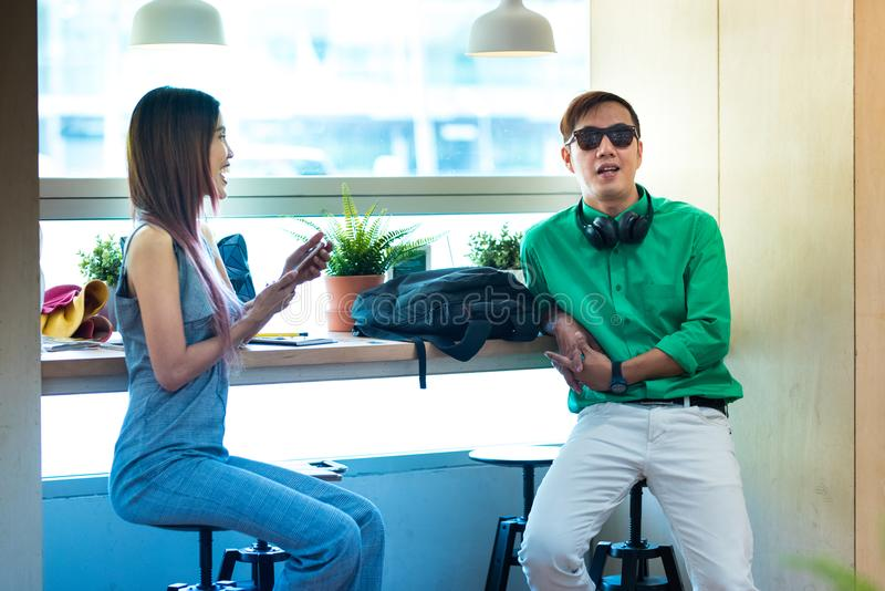 Asiatische Paare in der legeren Kleidung sitzen und sprechen in der Kaffeestube, modern lizenzfreie stockbilder
