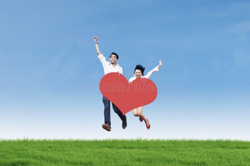 Asiatische Paare, die auf Gras mit Herzkarte springen lizenzfreie stockfotografie