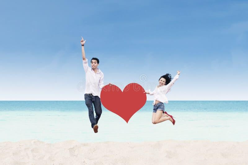 Asiatische Paare, die mit Herzkarte am Strand springen stockbild