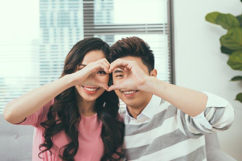 Asiatische Paare, die nah an einander sitzen und durch ein h schauen stockbilder