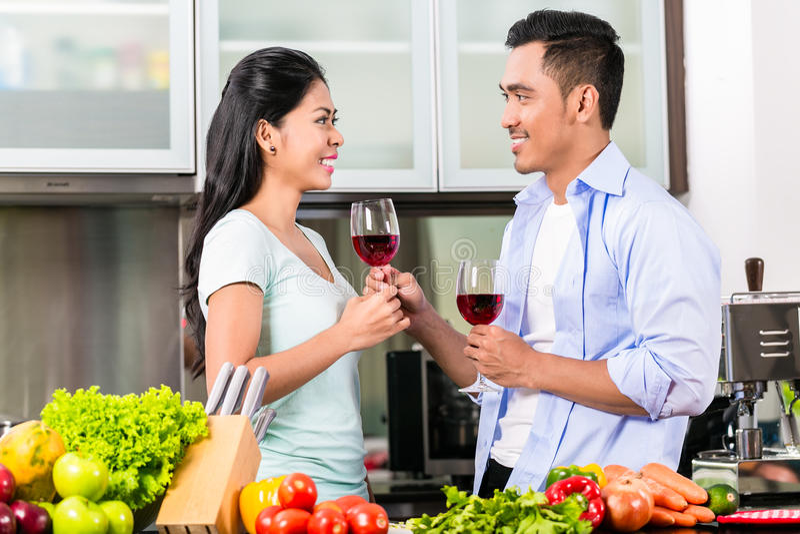 Asiatische Paare, die Rotwein in der Küche trinken stockbild