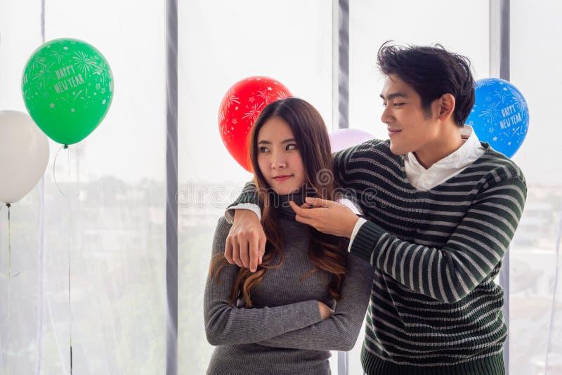Asiatische Paare tragen lange Pullover, organisieren zu Hause eine Neujahrsfeier Handlicher junger Mann, der versucht stockfoto