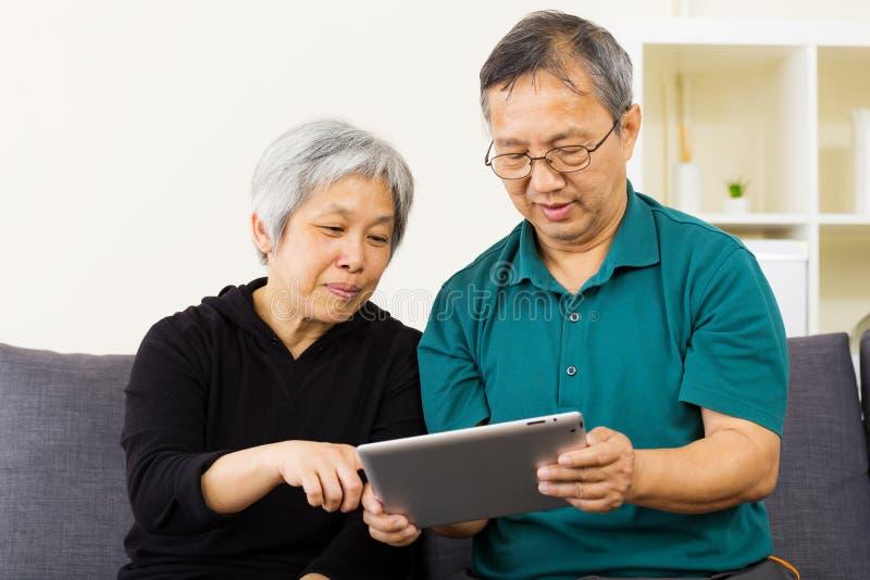 Asiatische Paare unter Verwendung der Tablette zusammen stockbilder