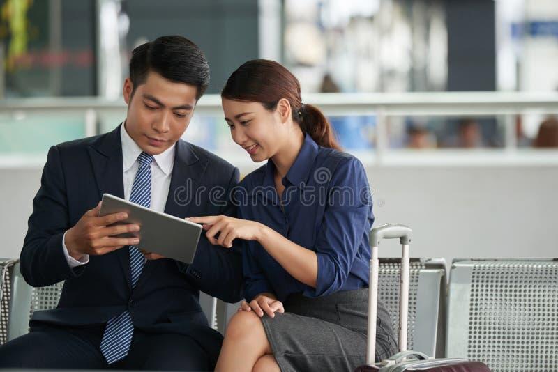 Asiatische Paare unter Verwendung des Tablets im Flughafen stockfoto