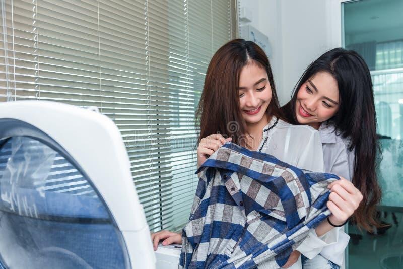 Asiatische Paarfrauen, die zusammen Hausarbeit und Aufgaben vor Waschmaschine tun und Kleidung in der Waschk?che laden Leute und lizenzfreies stockbild