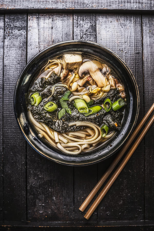 Asiatische Ramensuppe mit Nudeln, Tofu und nori Meerespflanze in der Schüssel mit Essstäbchen lizenzfreies stockbild