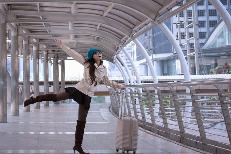 Asiatische Reisefrau lächelnd und glücklich zu tragendem Strickjackenmantel, Querstation lizenzfreies stockfoto