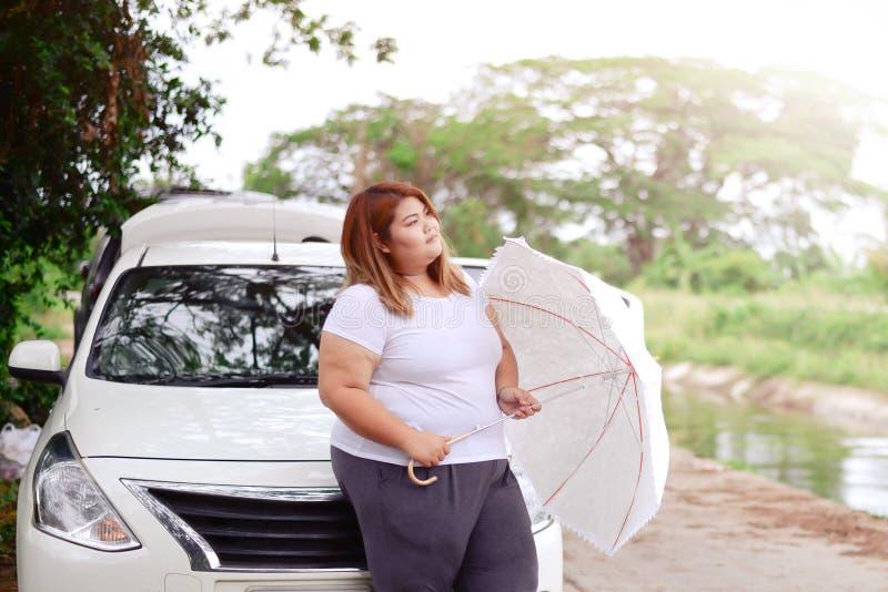 Asiatische schöne fette Frau mit Regenschirm im Garten stockbild
