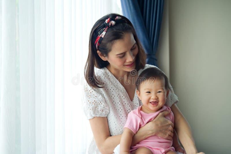 Asiatische schöne Mutter, die ihr nettes Baby in ihren Armen zu Hause sitzen nahe dem Fenster hält lizenzfreie stockfotografie