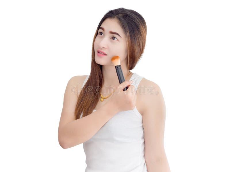 Asiatische Schönheit, die kosmetische Pulverbürste auf dem glatten Gesicht lokalisiert auf weißem Hintergrund anwendet Skincare stockfotografie