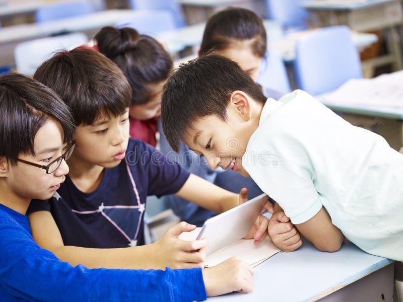 Asiatische Schulkinder, die zusammen digitale Tablette verwenden lizenzfreie stockfotografie