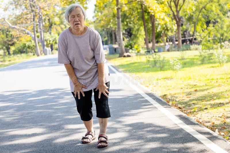 Asiatische Seniorin ist extrem müde beim Spaziergang im Park, der Körper ist schwach müde wegen Energiemangel und nicht stockbild