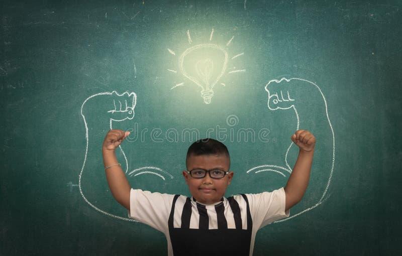 Asiatische starke Kinder gegen Tafel im Klassenzimmer, Bildungskonzept stockbild
