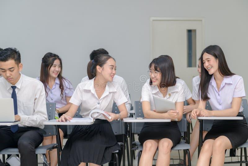Asiatische Studenten, die in einem Klassenzimmer und in einer Unterhaltung sitzen stockfotografie