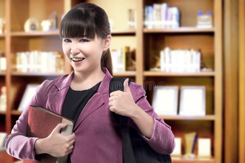Asiatische Studentenfrau mit tragender Buchstellung des Rucksacks in der Universitätsbibliothek stockfotografie