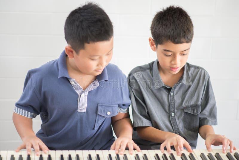 Asiatische Studentenjungen, die zusammen Klavier in der Klasse spielen lizenzfreie stockbilder