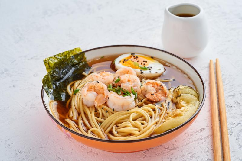 Asiatische Suppe mit Nudeln, Ramen mit Garnelen, Misopaste, Sojaso?e Weiße Steintabelle, Seitenansicht lizenzfreie stockfotos