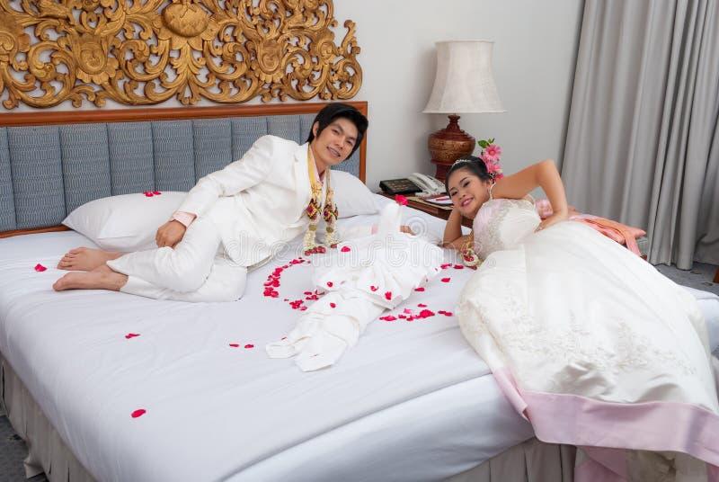 Asiatische thailändische Braut und Bräutigam auf einem Bett im Hochzeitstag lizenzfreie stockfotos