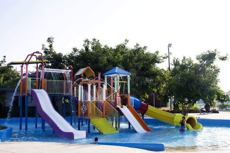 Asiatische thailändische Kinder entspannen sich das Spielen mit Freunden am modernen bunten Spielplatz stockbild