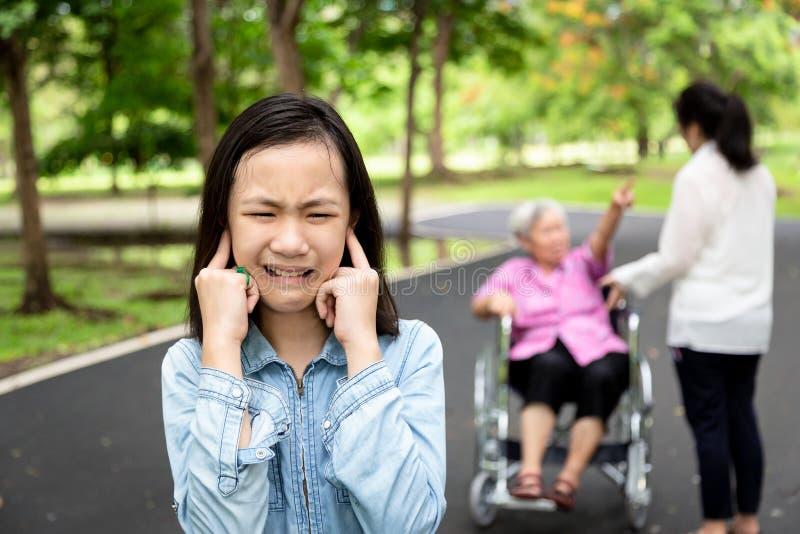 Asiatische Tochter schloss Ohren mit den Händen, kleinem Kind, die Mädchen nicht Eltern hören wollte, Großmutter im Rollstuhl und stockfotos