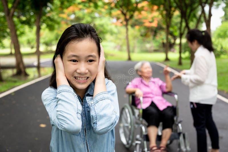 Asiatische Tochter schloss Ohren mit den Händen, kleinem Kind, die Mädchen nicht Eltern hören wollte, Großmutter im Rollstuhl und stockbilder