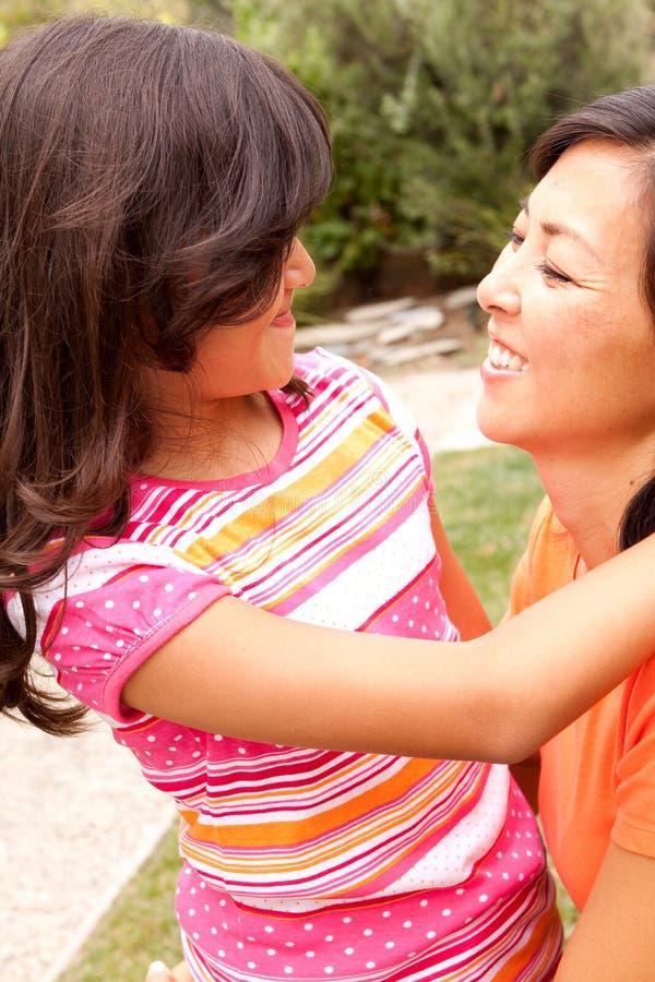 Asiatische umarmende und lachende Mutter und ihre Töchter stockfotografie