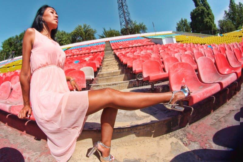 Asiatische vorbildliche Aufstellung am Stadion, das auf hellen Sitzen, heißer Körper, lange Beine sitzt lizenzfreies stockbild