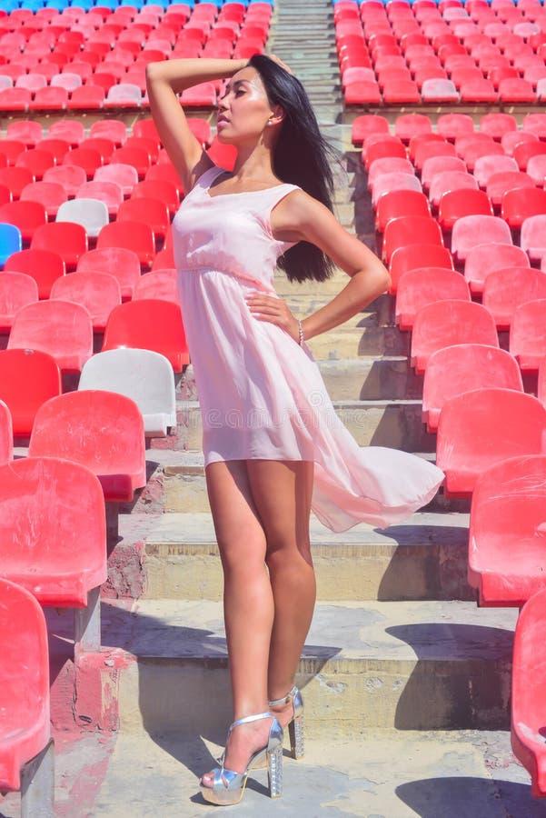 Asiatische vorbildliche Aufstellung am Stadion, das auf hellen Sitzen sitzt stockfoto