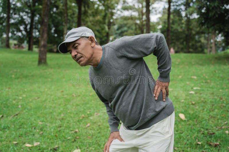 Asiatischer älterer alter Mann, der Rückenschmerzen hat stockbild