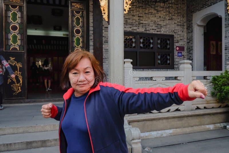 Asiatischer älterer Frauen Reisender machen eine Kung-Fu-Haltung vor Wong Fei-Hung Memorial Hall lizenzfreie stockfotografie