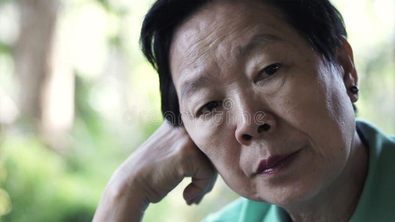 Asiatischer älterer älterer Frauensorgenausdruck, der an das Leben denkt stockbilder