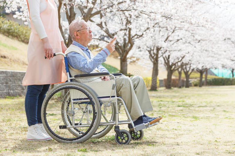 Asiatischer älterer Mann, der auf einem Rollstuhl mit dem Pflegekraftzeigen sitzt stockfotografie