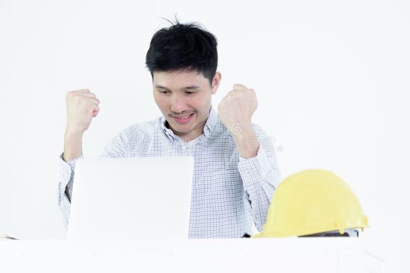 Asiatischer Angestelltingenieur-Gehaltsmann, der am Schreibtisch und an Arbeitsw sitzt lizenzfreies stockfoto