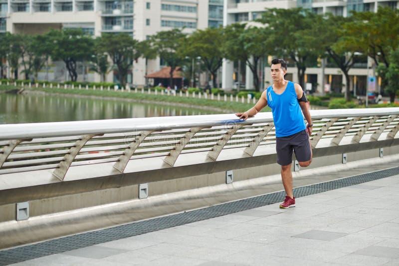 Asiatischer Athlet, der bevor dem Rütteln aufwärmt lizenzfreie stockfotografie