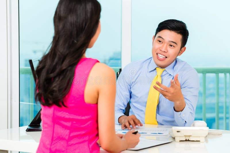 Asiatischer Berater mit Kunden auf Investition lizenzfreies stockbild