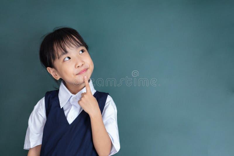 Asiatischer Chinese-kleines Mädchen, das mit dem Finger auf Kinn denkt lizenzfreie stockfotos