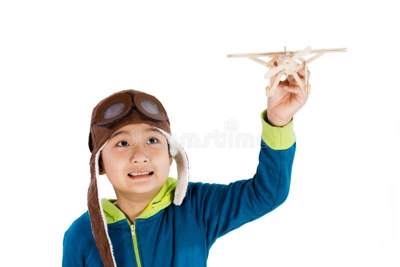 Asiatischer chinesischer Junge, der mit hölzernem Flugzeug spielt lizenzfreies stockfoto