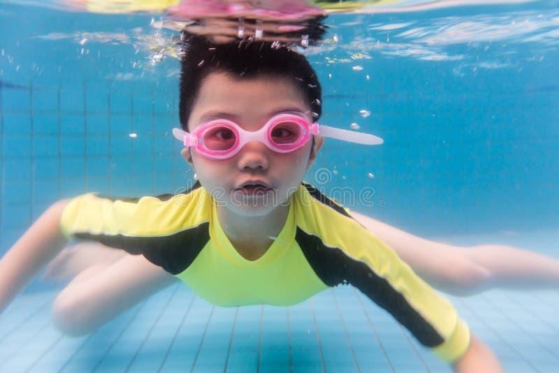 Asiatischer chinesischer kleiner Junge, der unter Wasser schwimmt stockfotos