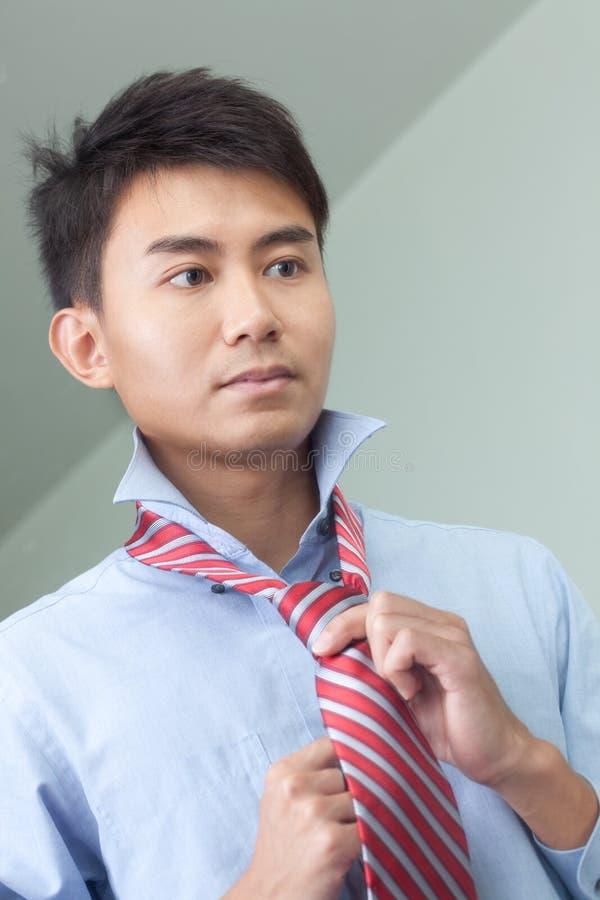 Asiatischer chinesischer Mann bereitet sich für Arbeit im Morgen vor stockfotografie